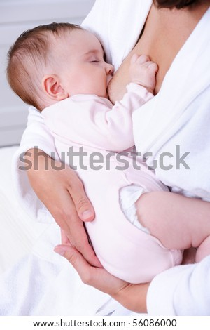 Little beautiful newborn baby eating milk from mother's breast