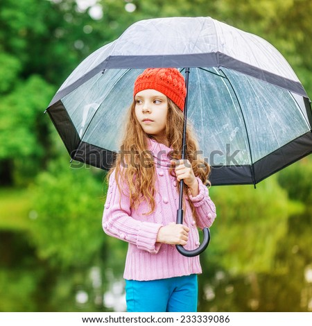 Little beautiful pensive girl in red cap and an umbrella on background of autumn park with lake.