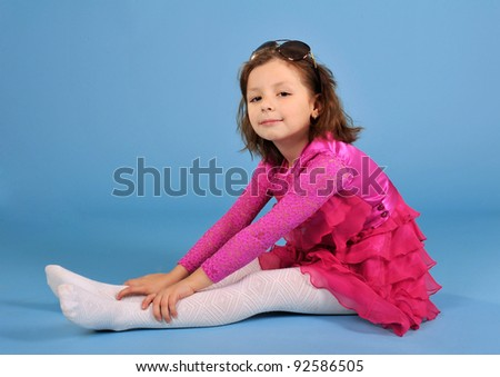 Little beautiful posing girl in purple dress and sun glasses
