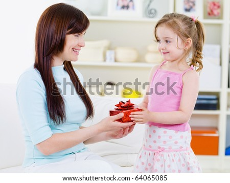 Little beautiful pretty girl giving a gift to her happy mother - indoors