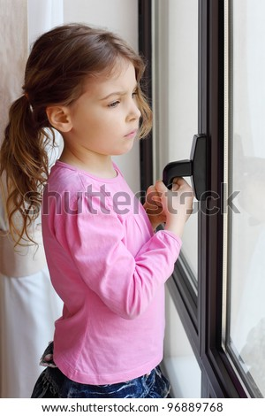 Little beautiful sad girl stands near window and holds handle of frame