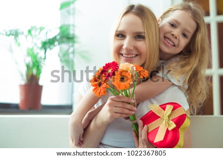 Little beautiful smiling girl hugging her mother and gives a gift in a box and a bouquet of flowers. Mothers Day. March 8. Women's Day. #1022367805