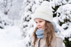 Little beautiful stylish girl in winter hat, woolen coat, blue scarf, snood with long hair. Kid walking, playing in forest, park among trees covered with snow. Country house yard. Fashionable image.
