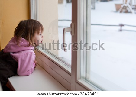 Little beauty girl  look out of the window and breathe on the glass so that it grow misted. Winter.