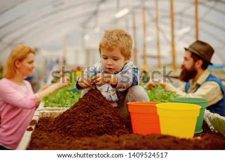 little biologist. little biologist work with soil. little biologist in greenhouse. little biologist child planting flowers #1409524517