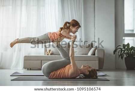 Little bird. Mother is lying on her back and holding her daughter on her feet during fitness at home. Girl looking happy while woman is laughing
