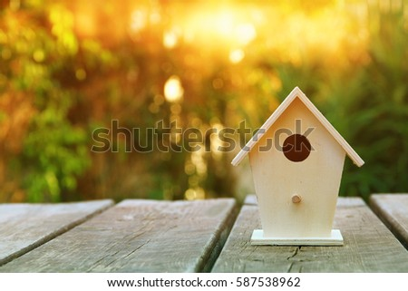 Little Birdhouse over wooden table outdoors in the garden