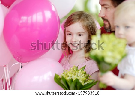 Little birthday girl with pink balloons and flowers