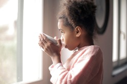 Little Black girl drinking tea at the window.