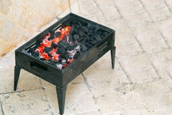 Little black grill with coals against the background of pavement