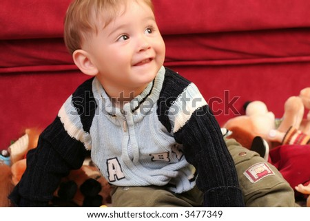 Little blond baby boy playing with toys at home