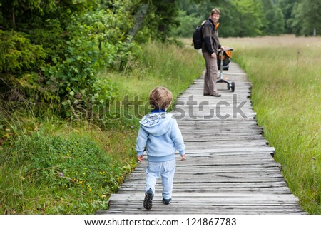Little blond boy and his father walking through nature park summer