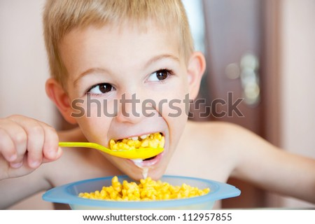 Little blond boy eating corn flakes with milk