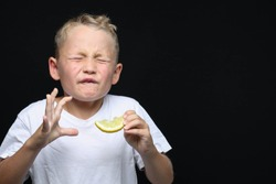 Little, blond boy is eating a piece of a lemon in front of black background and making a facial expression.