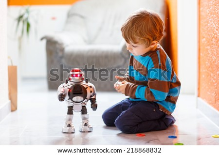 Shutterstock Little blond boy playing with robot toy at home, indoor