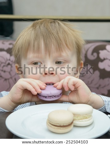 little blond boy sitting at a table eating cake