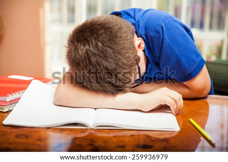 Little blond boy taking a nap in the middle of a difficult homework