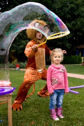 little blond girl and lion playing with soap bubble at the kids birthday party