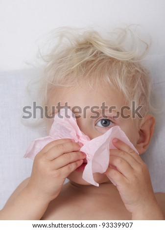 Little blond girl blowing her nose