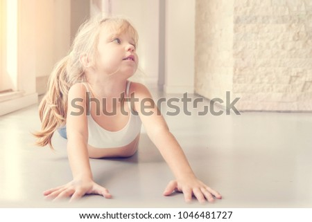 Stock Photo Little blond girl doing stretching exercises in the sunny room