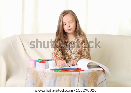 Little blond girl drawing at home on sofa