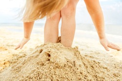 Little blond girl having fun and playing on the beach,burying her feet in a sand.