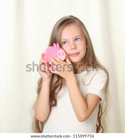 Little blond girl hearing how much money in piggy moneybox and dreaming about future purchase