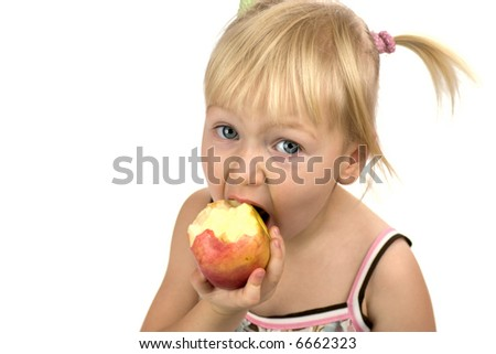 Little blond girl in process of eating tasty big red apple