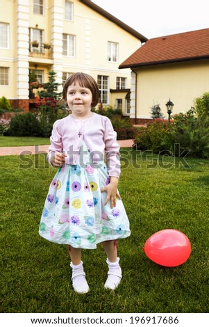 little blond girl in the mansion house garden with red ball