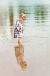 little blond girl in the pastel dress is standing in the water and looking at her reflection