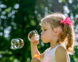 Little blond girl in white shirt blowing soap bubbles