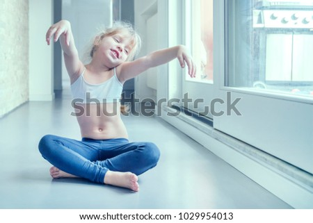 Stock Photo Little blond girl in white top and blue leggings doing a yoga exercise in the room