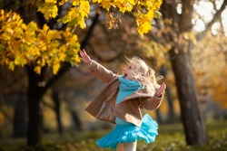 Little blond girl jumping to the autumn leaves in the park. Cute girl have fun on a warm sunny day. Happy emotions, outdoor activities in autumn. Selective focus.
