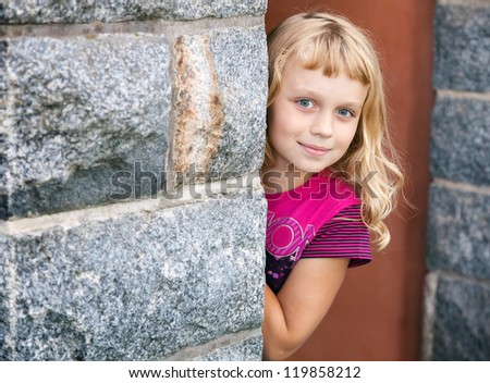 Little blond girl looks out from behind the gray stone wall and smiles