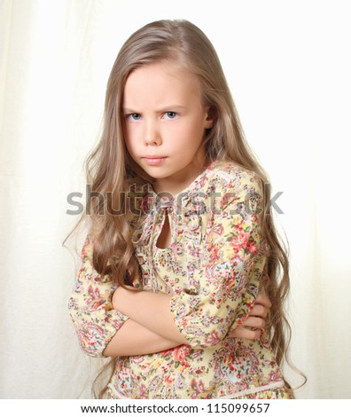Little blond girl posing with crossed hands on her breast