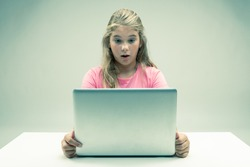 Little blond girl staring at her laptop in astonishment with her eyes wide and mouth open in surprise as she sits at a white table over a studio background