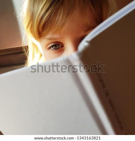 Little blond girl wearing big eye wear reads a book