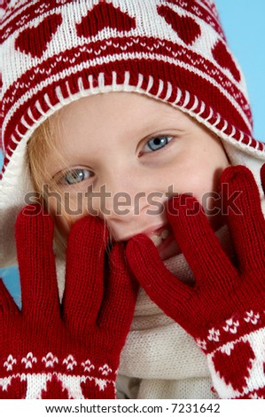 Little blond girl wearing woolen cap, scarf and gloves