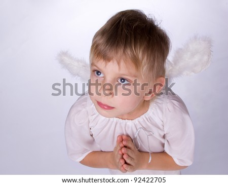 little blond girl with angel wings praying