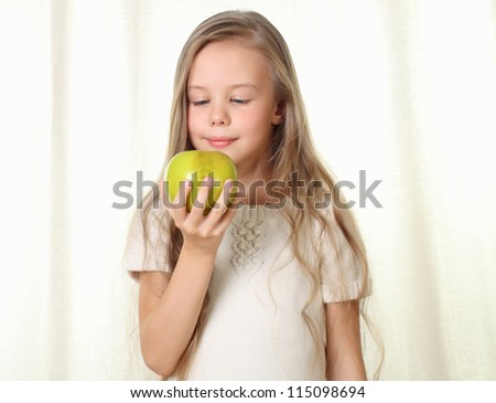 Little blond girl with apple looking on it and sniffing with appetite