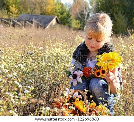 little blond girl with autumn flowers in a country meadow