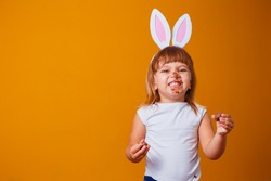 Little blond girl with dirty chocolate bunny ears eating Easter egg