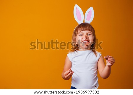 Little blond girl with dirty chocolate bunny ears eating Easter egg Stock photo ©