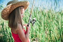 Little blond girl with straw hat prepares her fishing rod sitting near the lake