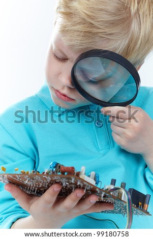 Little blond guy looking at a mother board through magnifying glass