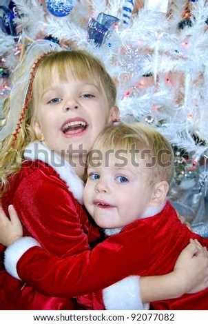 little blond sisters hugging by white Christmas tree