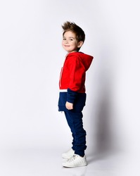 Little blond son in a blue and red tracksuit, sneakers. Smiling posing sideways isolated on a white background. Childhood, fashion, advertising, sport concept. Full length, copy space