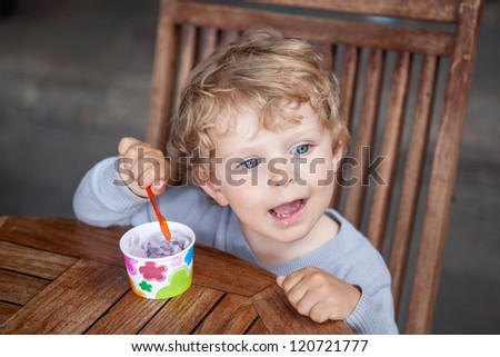 Little blond toddler eating ice cream in self made ice cream cup