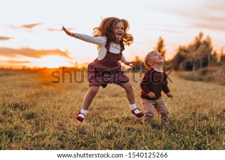 little blonde children outdoors brother and sister