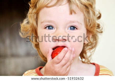 little blonde curly girl eating fresh strawberry